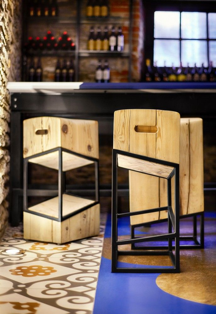 """Barsa Taberna / +tongtong // Enclosing the bar are custom-designed stools made of salvaged, old-growth pine with an powdered coated steel frame. Dubbed the """"little pest,"""" or in Spanish """"becho mio"""" the stool has three variations. With tops resembling worn butcher blocks and carved-out handles that riff on the forms of old wine crates, the stools are a nod to the traditional tapas eateries, where seats are fashioned out of old wine barrels, wooden crates, or whatever is available."""