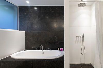 Také na obkladech koupelny se opakuje tmavě šedá barva.