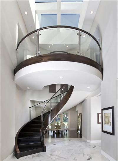 Elegant Contemporary Foyer by Mark English - This dramatic, two-story circular staircase is a compelling centerpiece that sweeps your eyes upward to the skylights and the blue skies above.