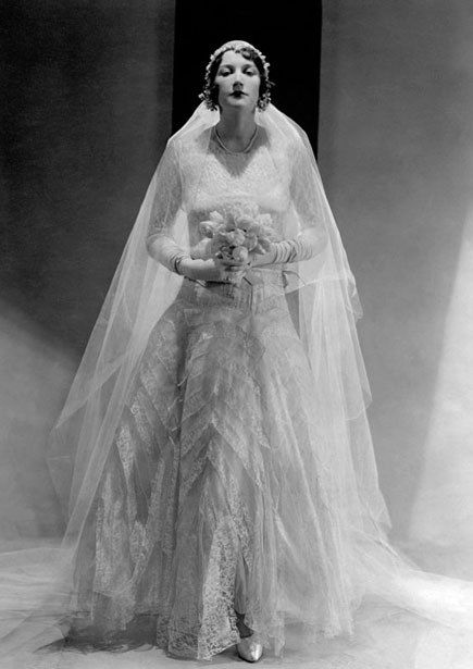 This stunning gown is Chanel—long-sleeved and worn with gloves—and is made entirely of stiffened lace, worn by bride Betty Garst.