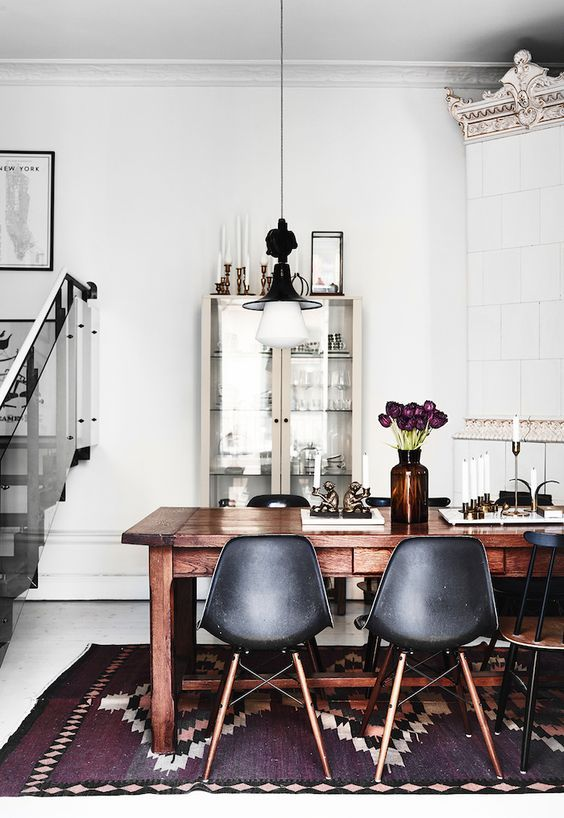 Scandinavian dining room with light fixture and printed rug