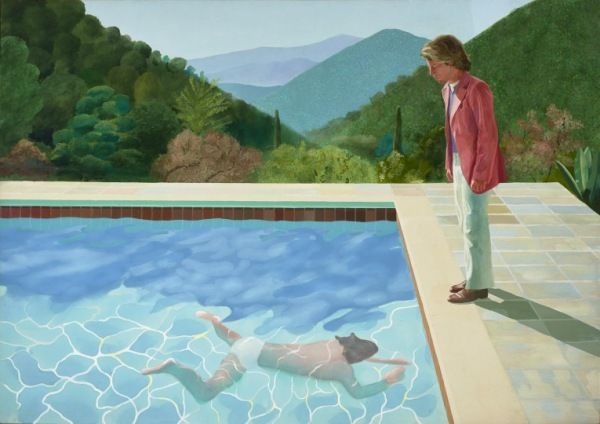 A man watches another man swimming in a swimming pool with a hilly wooded scene in the background.