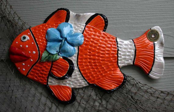 Afmetingen: 18 x 11 (L x B) (inch)  Absolute houding Nemo clown-vis draagt een eiland hibiscus achter zijn fin. De Clown vis heeft een heldere wildvuur oranje glazuur met zwarte vlekjes, witte reliëf en gedetailleerd met zwart. De munt van welvaart op de staart toont de Phoenix rising, een wedergeboorte van de as. Een tijd na te denken over onze Oceaan en verhalen van Davy Jones Locker. Prachtige rode lippen en witte sproeten maken dit stuk een must have voor uw interieur…