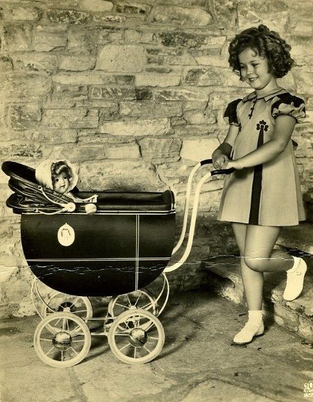 1936 Shirley Temple poses with an Ideal Shirley Temple Baby in a Whitney Shirley Temple Doll Carriage at her Brentwood home