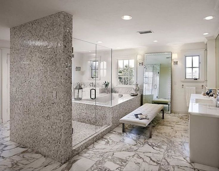 The pattern of the tile shower and tub enclosure contrasts with the vein of the floor. A large padded bench sits adjacent to the bathtub.