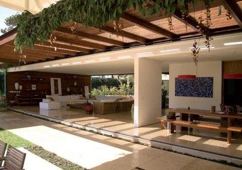 A varanda foi ambientada com móveis e tecidos da Artefacto. Treliça de madeira foi o recurso utilizado pelas profissionais para dar privacidade ao local. A árvore-da-felicidade traz vida ao espaço, que possui piso de pedra Goiás.