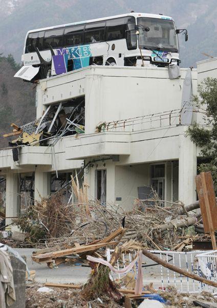 大津波で半壊した建物の上に運ばれたバス(宮城県石巻市の雄勝地区)(2011年03月21日) 【時事通信社】