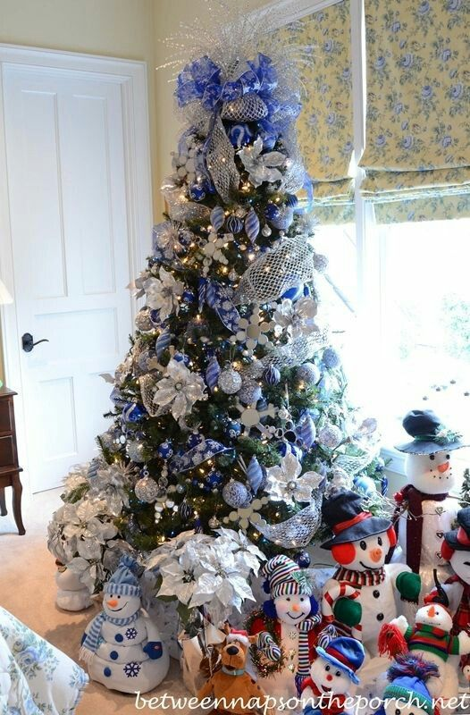 Deep blue decorated Christmas tree w/a snowman collection.