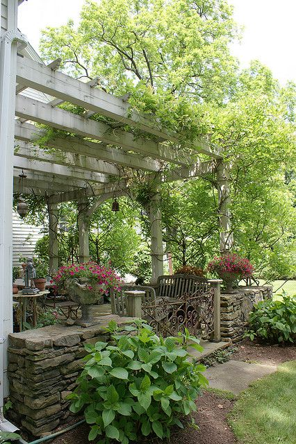 Sweet pergola patio design.  Love the plants.