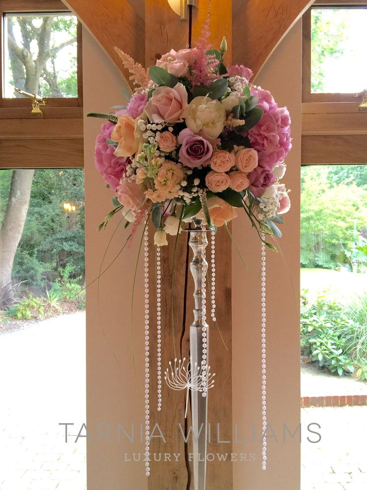 Pink peonies and peach roses on silver candlesticks for the ceremony at Rivervale Barn by www.tarniawilliams.co.uk