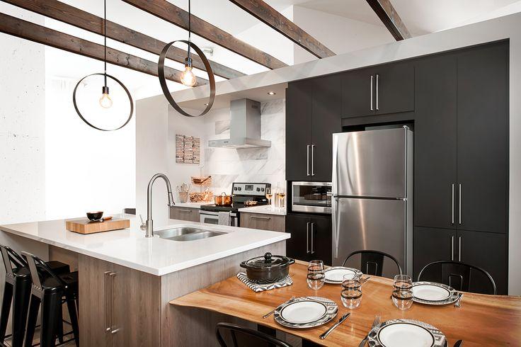 Un style moderne et contemporain avec de beaux contrastes de teintes. Une inspiration de loft aux allures modernes, un espace rassembleur pour les soirées huppées bien animées. Un mélange de texture est présenté avec les choix de matériaux de cette cuisine, un mélange de foncé mat et un grain de bois linéaire.