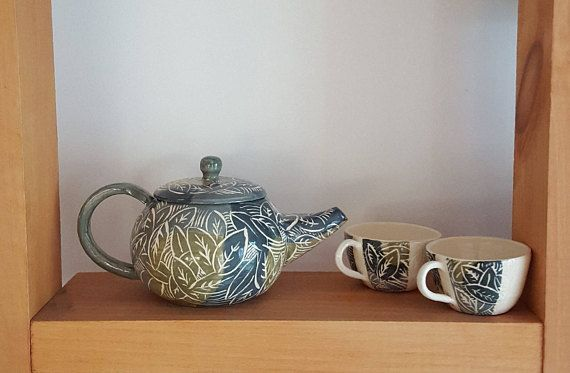 Ceramic handmade teapot or tea set with jungle print carving. Perfect as a gift or to add something special to your morning. This teapot measures approximately 8.5 long, 5 wide and 4.5 tall. The each tea cup measures approximately 3 wide by 2 tall. However, my work is all completely handmade and therefore each piece will be slightly different in terms of color hue and size. These ceramics are dishwasher safe, and non-toxic.  This listing is for one carved teapot, with different combinations…