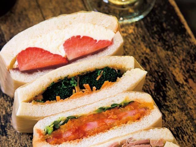 《 渋谷 》上からほど良い甘さの「苺とあんこクリーム」(¥380)、茹でたブロッコリーとたっぷりの千切りにんじんが入った「ブロッコリーとピーナッツバター味噌」(¥170)、さっぱりとしたソースが美味しい「トマトソースのハムカツ」(¥180)。  サンドイッチ片手に一杯飲める! 『ドレスのテイクアウト店』のサンドイッチ各種  「ドレスのテイクアウト店」という店名のとおりテイクアウトを主とするけれど、イートインも楽しむことができる。3席しかないが、この席が狭いながらなんとも落ち着くのだ。   サンドイッチはどれもひと工夫されており、ここでしか食べられない味わい。味の基準となるのは、酒のつまみになること。バーで働いた経験もある店主が作るサンドイッチは、酒に合うようしっかりと味付けがされていたり、食感がいい野菜がたっぷり入っていたり…と、店主の細やかな工夫が光る逸品ぞろいだ。   もっちりとした塩豚とパクチーがマッチした「塩豚パクチー¥220」、セロリの食感とオリーブの塩気が絶妙な「ツナセロリオリーブ¥180」。これら絶品サンドイッチにはワイン(1杯¥500)などを合わせて楽しみたい。