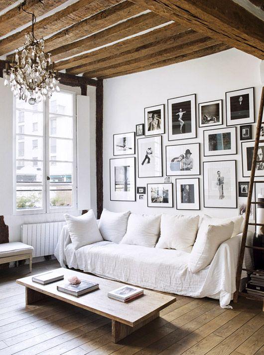Reformas que exprimen el carácter de lo que se tiene. Salón techos altos de madera. Decoración blanca, suelo madera.