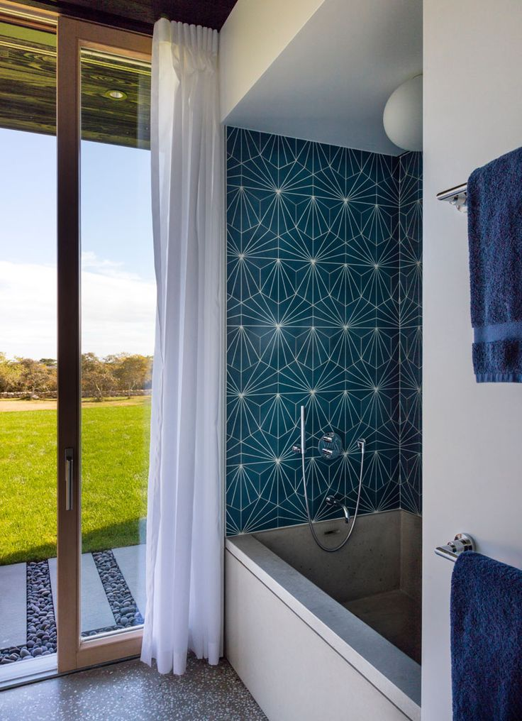 In this modern bathroom, colorful blue patterned tiles have been used to highlight the bath and add some color to the room, while a sliding glass door provides direct access to the backyard.