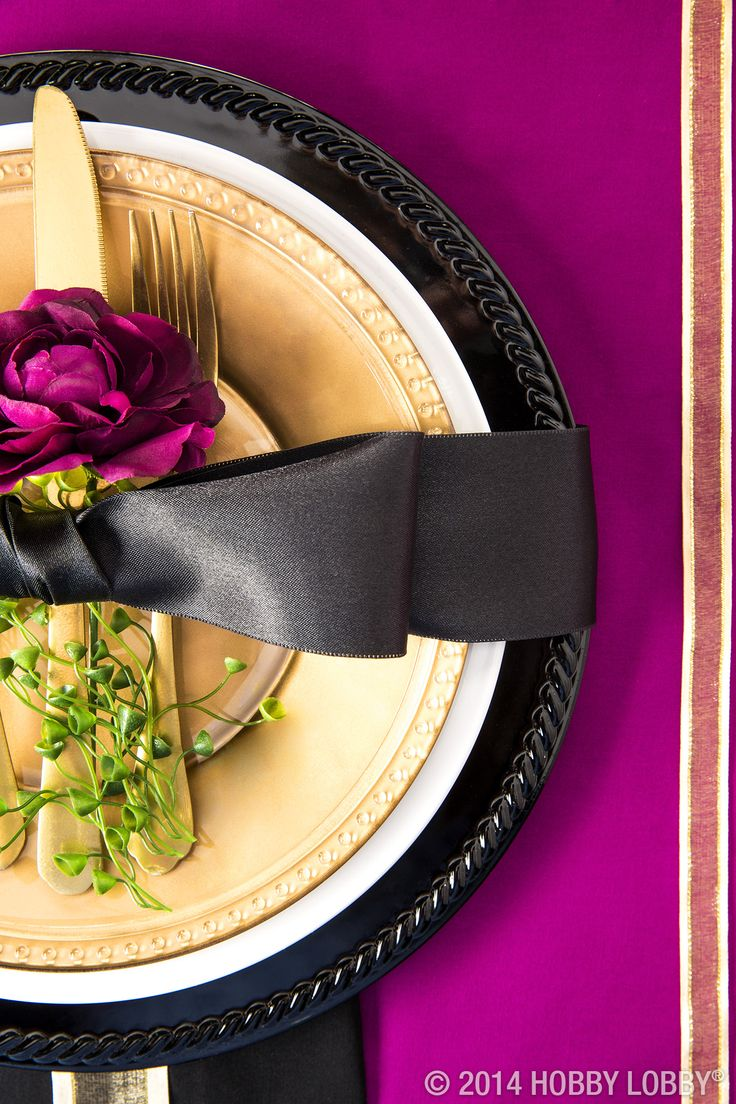 Tie a metallic place setting together with a big bow and a single floral stem. This look is timeless and elegant.