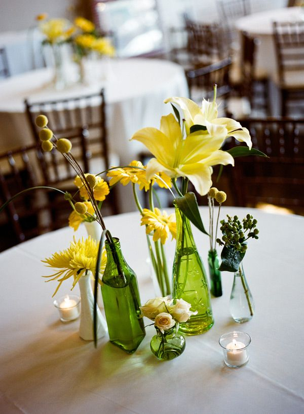 A variety of yellow flowers n interesting green and clear bottles make an interesting centerpiece.    Southern weddings - green bottle centerpieces