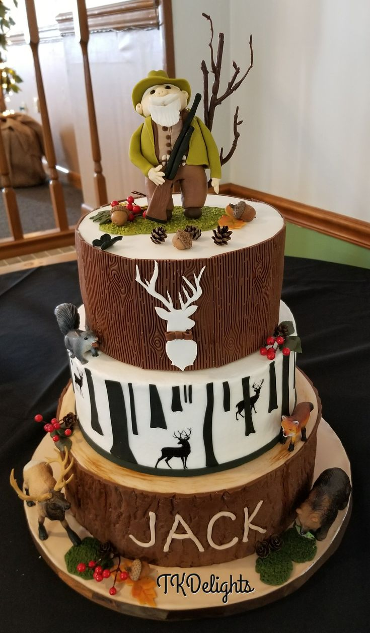 8oth birthday Hunter cake All white cake with strawberry buttercream filling.  Top and bottom layers covered in fondant.  Middle tier is buttercream with fondant trees and edible images deer. Fondant Hunter and toy animals.