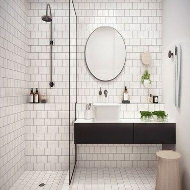 Cette petite salle de bain contemporaine en carrelage blanc est aménagée avec une douche italienne et un plan vasque suspendu noir qui libère l'espace au sol.