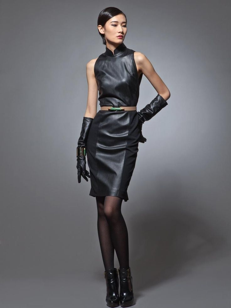 Asian girl in black leather sleeveless dress, gloves, and ankle boots. Runway fashion.