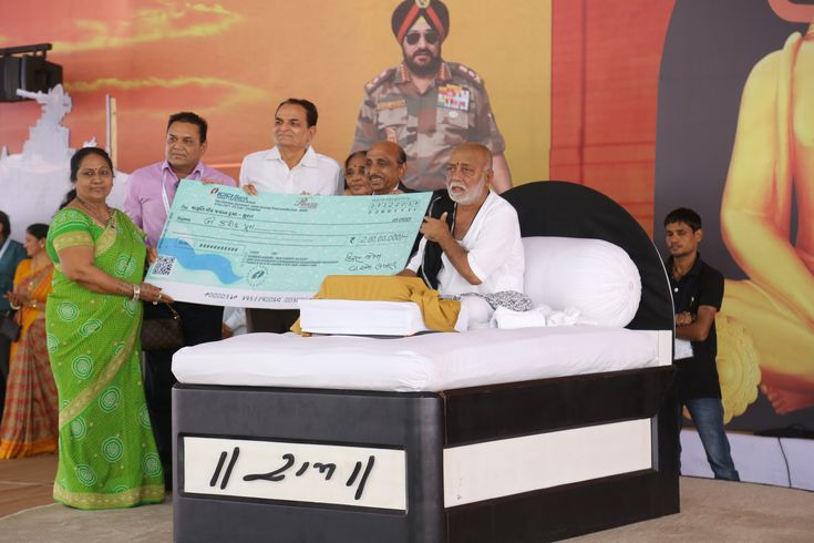 Smt. Laxmiben V. Patel (left) and Shri. Vallabhbhai Patel (in center) - Chairman, Kiran Gems Pvt. Ltd offering cheque to Morari Bapu during the Ram katha organized by Maruti Veer Jawan Trust for the Families of Indian Soldiers.  Visit our FB page: https://www.facebook.com/KiranGems/