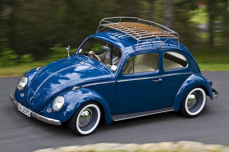 Royal Blue Bug with white walls and a wooden roof rack.
