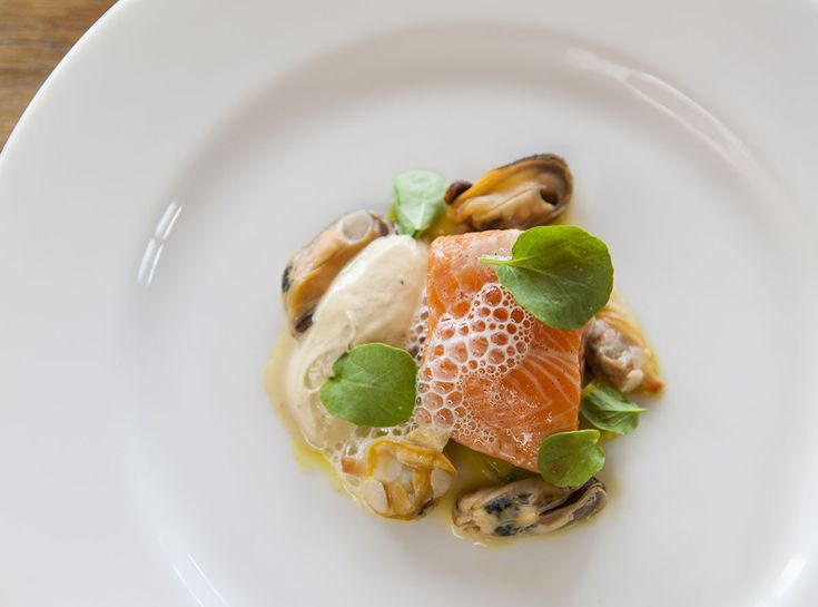 Our Chefs | Ōra King Salmon Dish by Daniel Wilson, Huxtable, Melbourne, Australia.  Vanilla Confit Ora King Salmon with smoked oyster cream, saffron braised leeks, mussels, clams and watercress #oraking