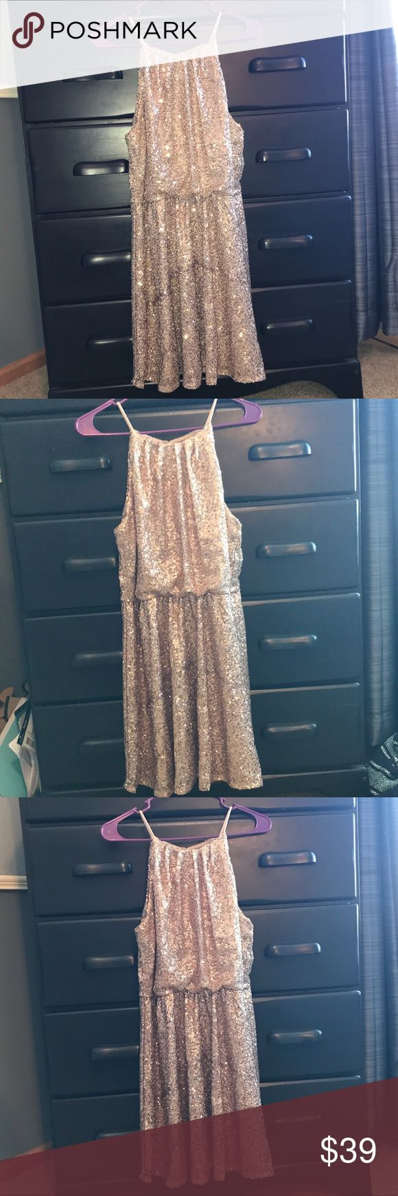 Gold Shimmer Fit and Flare Dress Valentines Day Beautiful gold shimmer dress with tiny gold sequins. It is high neck and hits about mid thigh. Has a beautiful open back details with a button at the neck. Elastic waistband. Great for the holidays or Valentine's Day. Make an offer! Forever 21 Dresses