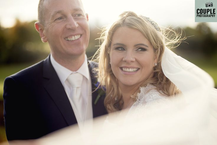 The bride & groom smile as the wind catches the bride's veil. Weddings at The Heritage Hotel by Couple Photography.