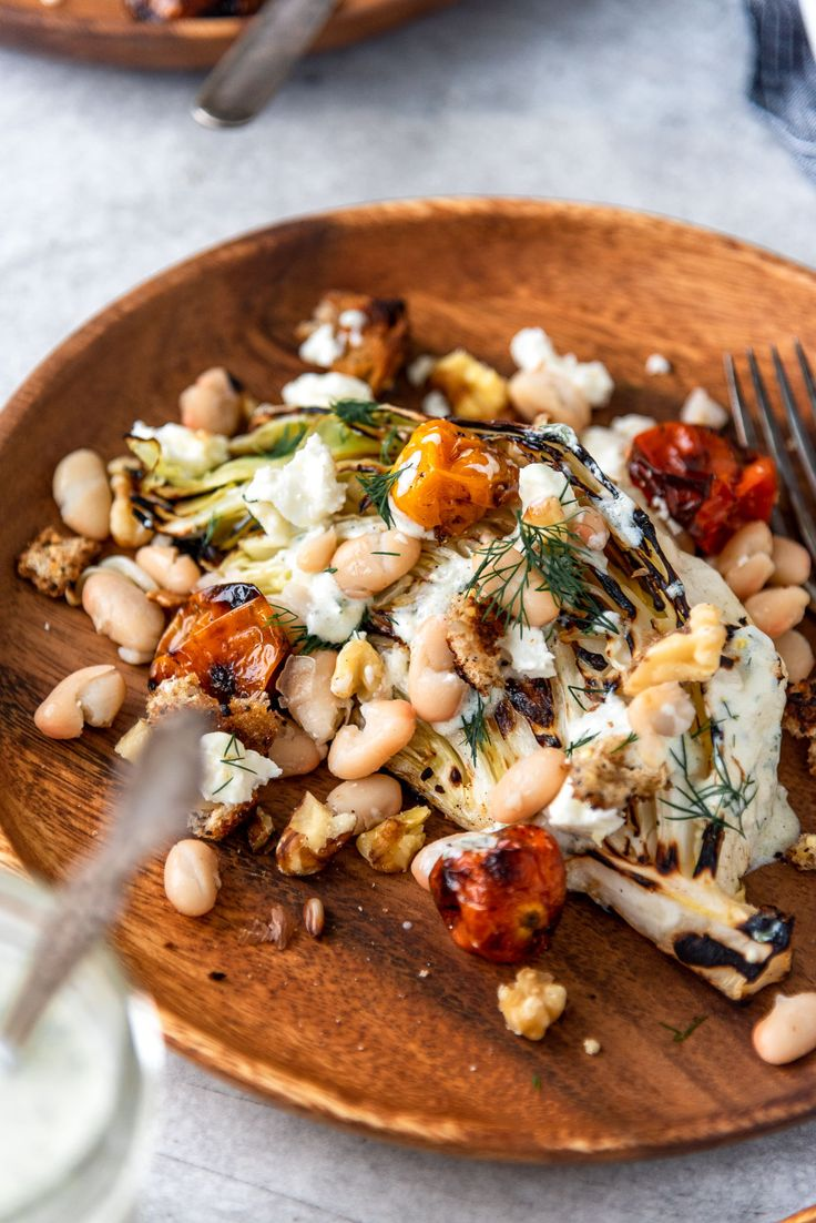 Jun 30, 2020 – Grilled Cabbage Wedge Salad topped with charred tomatoes, white beans, feta, walnuts, rustic grilled crou…
