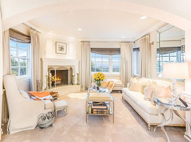 The room's all-white seating area has a fireplace and stunning views.