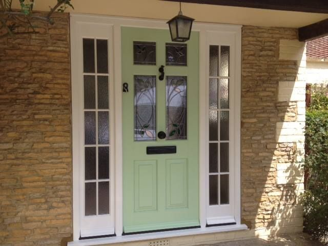 Timber entrance door in Fireglass Green with a white frame and cill. The glazing in the door is in Willow green. Side panels are obscure and feature astragal bars.