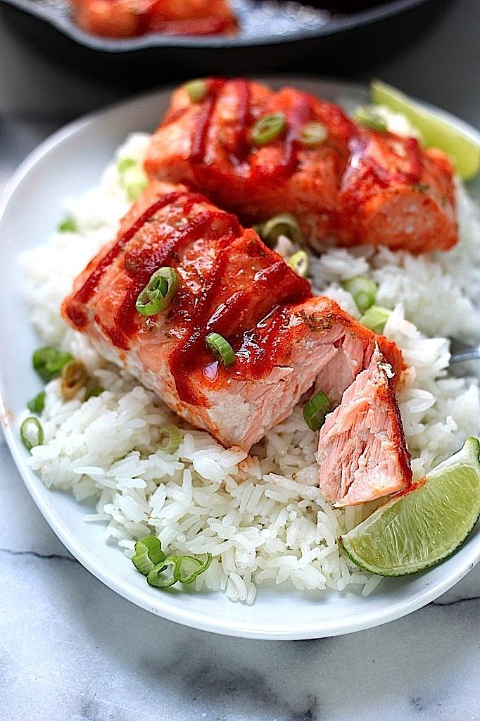 Sweet and Spicy Sriracha baked Salmon with rice and a twist of lemon on the side, great tasting meal.