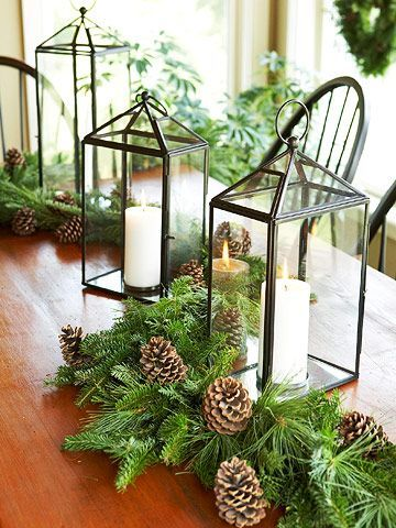 Construct an organic table display that will be appreciated long after mealtime. Here, pinecones and fresh greenery surround rustic steel-framed lanterns, conveying the atmosphere of the casual outdoors.