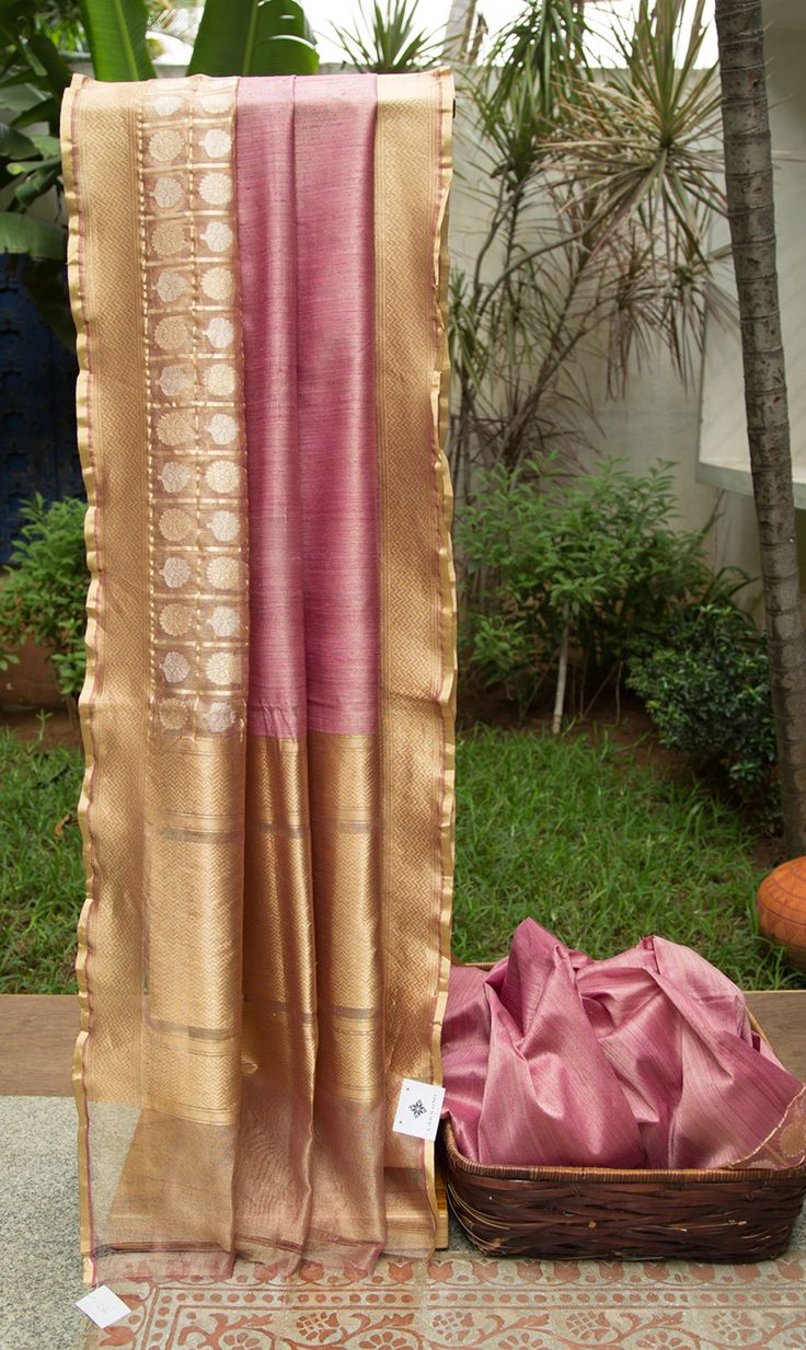 This elegant benares net sari is onion pink colored and has gold zari running all over to give it that extra shimmer. The border has a checkered pattern all over with traditional bhuttas woven in g…