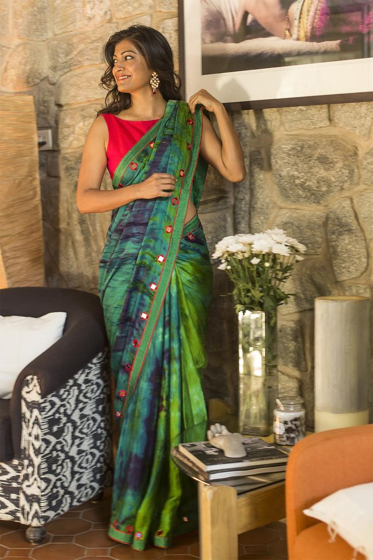 Open the way to a stylish season in this much coveted shibori dyed saree with beautiful all over detailing in red mirror work. This oh-so-soft satin saree drapes like a charm giving you an enviable sillhouette and warming you like a gentle hug. Designed with a show-stopping green and red pallu in raw silk also extensively detailed in mirror work, pick this wonder to keep the compliments pouring in. #green #shibori #mirrorwork #saree #India #blouse #houseofblouse