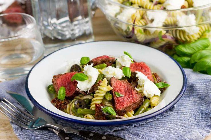 Recept voor italiaanse pastasalade voor 4 personen. Met zout, boter, olijfolie, peper, aluminiumfolie, sperzieboon, zwarte olijven, zongedroogde tomaten in olie, biefstuk, Pasta, basilicum, mozzarella, rode ui en groene pesto
