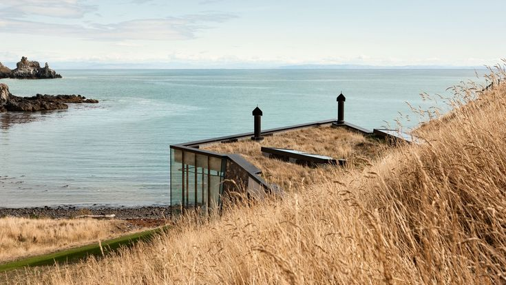 Seascape Retreat by award winning, Auckland-based Pattersons Associates Architects can only be described as heaven on earth. Located on the Banks Peninsula in the majestic volcanic landscape of New Zealand's South Island, this modern cottage retreat is set within a rock escarpment in a remote private bay, and is accessible by helicopter or by 4-wheel-drive vehicle across the cliff-top farm tracks.