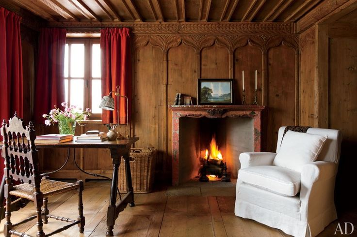 In the second master bedroom, a 19th-century painted mantel offsets the honey-tone paneling; the 17th-century table is paired with a circa-1600 Spanish chair.  .. Studio Peregalli Creates a Rustic Home in the Swiss Alps Photos | Architectural…