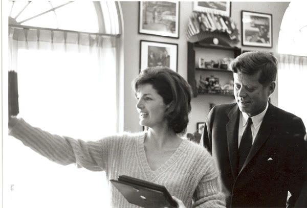 Jackie holding up photos to put in the oval office while her husband is helping out at the white house oval office.