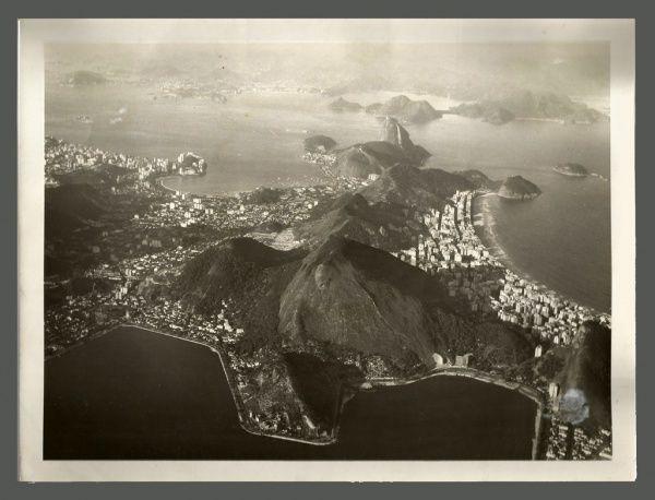 CARLOS BOTELHO. Fotografia aérea panorâmica do Rio de Janeiro, tomada de grande altitude, carimbada no verso, numerada e datada 12 JUN 1955. 18 x 24 cm. Interessante composição com os espelhos dágua da Lagoa, da Baia de Guanabara e da Praia de Copacabana emoldurando a cidade.