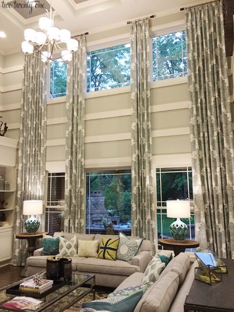 two story living room with floor to ceiling curtains