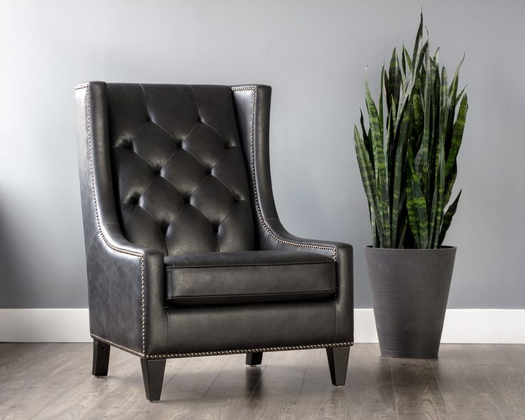 OHIO ARMCHAIR - Coal black faux leather armchair with antique brass nail heads and deep tufting in seatback