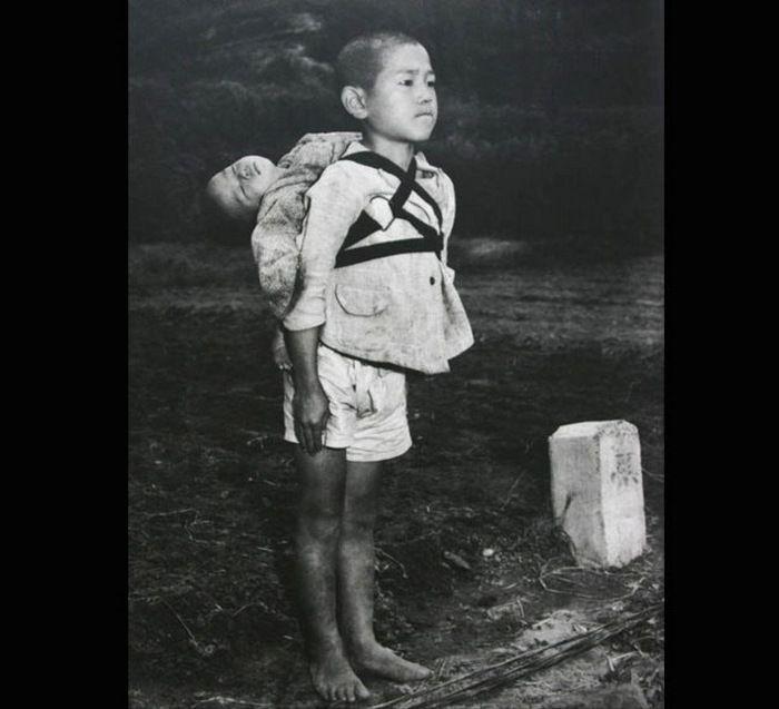 Фотография была сделана американским морским пехотинцем Джо О'Доннеллом вскоре после бомбардировки Нагасаки. Младший ребенок на фото мертв, а старший брат принес его на спине в крематорий. Старший мальчик остался и наблюдал, как его брата сожгли, при этом он не проронил ни слезинки, только закусил губу до крови. Мальчик только что потерял все после атомной бомбардировки, но он босиком принес тело своего родного брата, чтобы гарантировать ему достойные похороны.