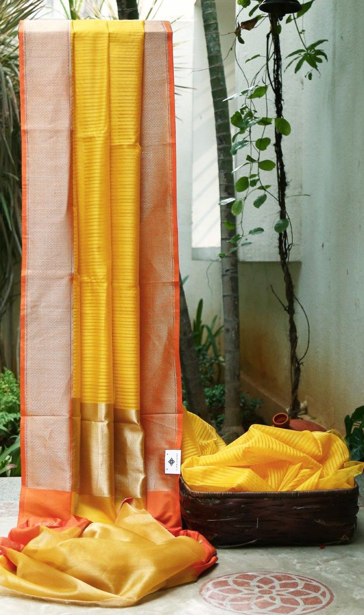 Striped yellow kora silk. The orange and gold border which flows into the pallu completes this piece