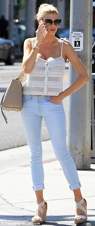Summer chic: The model paired her crochet top with light denim skinny jeans and wedge sand...