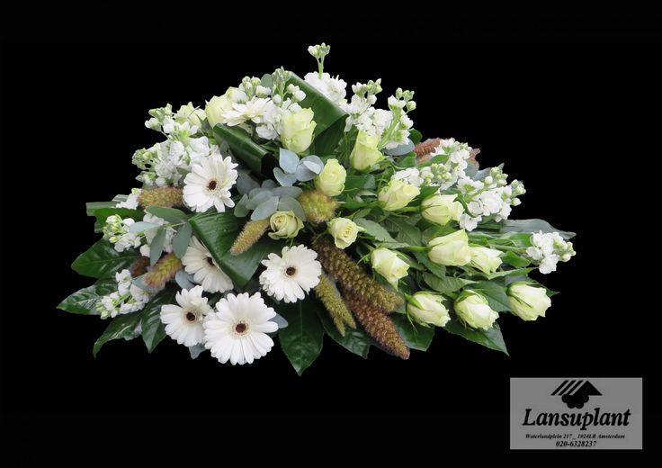 Rouwstuk druppelvorm op groepen met witte rozen, gerbera's, violieren. Gemaakt door bloemenwinkel Lansuplant Waterlandplein Amsterdam