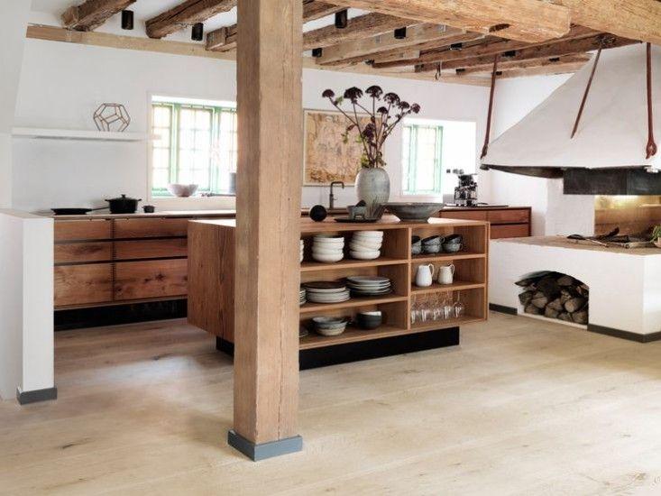 Holzbalken an der Decke. Holzfronten für Schränke. Kochkamin. Kochinsel mit Regal für Geschirr anstelle Hocker.