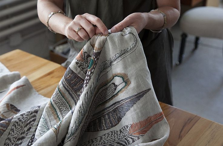 Housley shows off the intricate stitchery on a feather-festooned table runner.