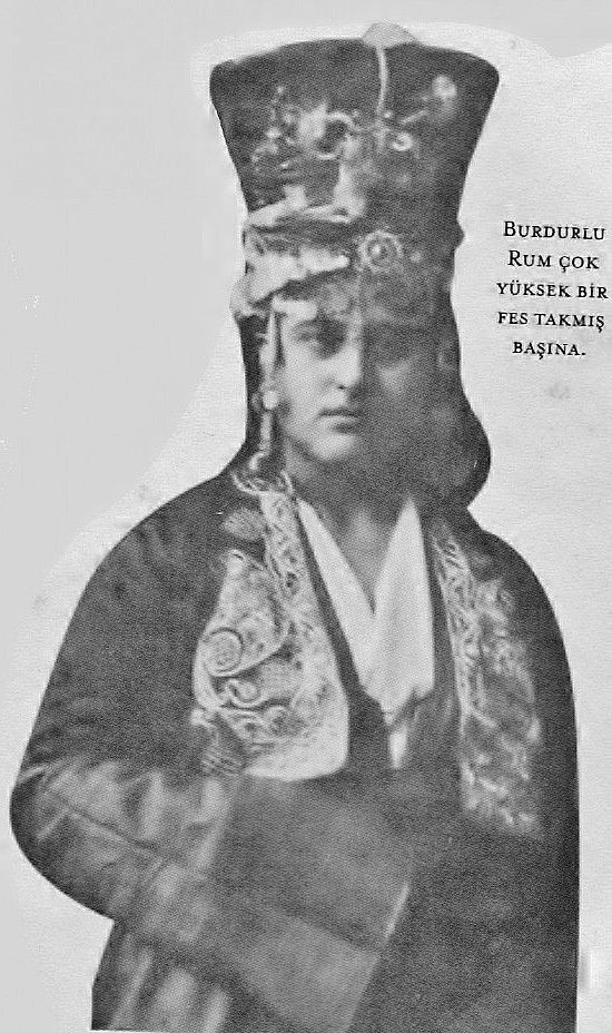 A 'Rum' (Anatolian Greek) woman in festive costume, which includes a very high hat.  From Burdur, urban fashion, ca. 1870.